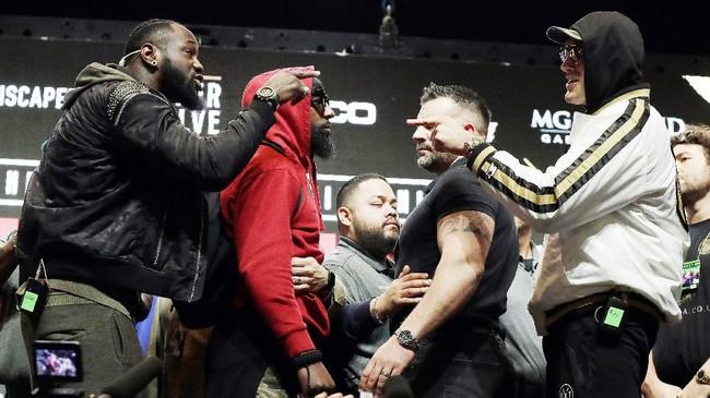 Beruntung kubu kedua petinju berhasil memisahkan Deontay Wilder dan Tyson Fury sebelum baku hantam terjadi. (AP Photo/Isaac Brekken)