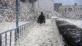 Seorang pria berjalan sementara buih-buih air laut menerpanya di Saint-Guenole, Perancis bagian Barat. Saat ini Britania Raya sendiri sedang disapu badai Dennis. (Photo by Fred TANNEAU / AFP)