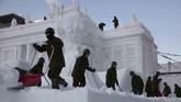 Anggota Angkatan Bersenjata membersihkan tumpukan salju pada patung Istana Polandia yang dibangun di Festival Salju Sappporo di Jepang. (AP Photo/Jae C. Hong)