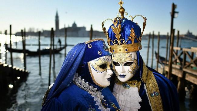 Peserta menggunakan topeng dan kostum ambil bagian dalam Karnaval Venice. (Photo by Alberto PIZZOLI / AFP)