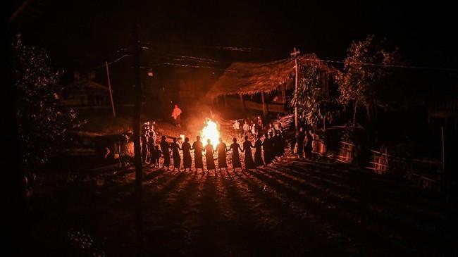 Perempuan-perempuan suku Naga di Satpalaw Shaung, kota Sagaing, Myanmar, mengelilingi api unggun dalam suatu ritual pemberkatan hasil panen. (Photo by Ye Aung THU / AFP)