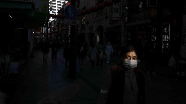Seorang turis bertopeng berjalan di pecinaan di kota Yokohama, dekat Tokyo. Meski saat ini Jepang waspada pada virus Corona, Olimpiade 2020 yang dijadwalkan berlangsung pertengahan tahun tidak akan dibatalkan. (AP Photo/Jae C. Hong)