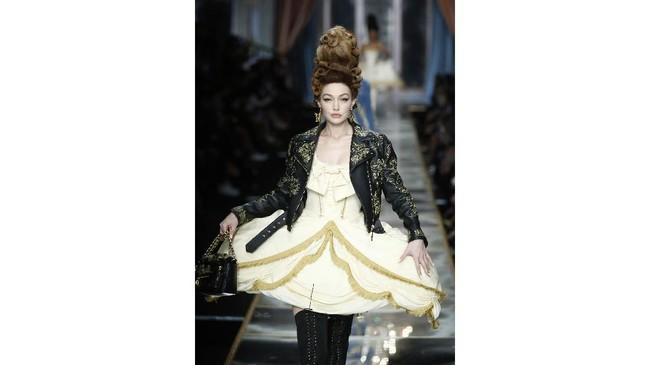 Model Gigi Hadid mengenakan jaket kulit bergaya biker dengan studs keemasan, dan mengenakan gaun pannier serta over-knee boots. Sebuah kombinasi antara pesona antik dan tren kontemporer yang sangat baik. (AP Photo/Domenico Stinellis)