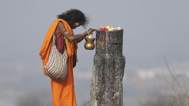 Seorang suci terlihat berdoa di shivling, representasi Dewa Siwa dalam festival Maha Shivaratri di India. (AP Photo/Mahesh Kumar A)