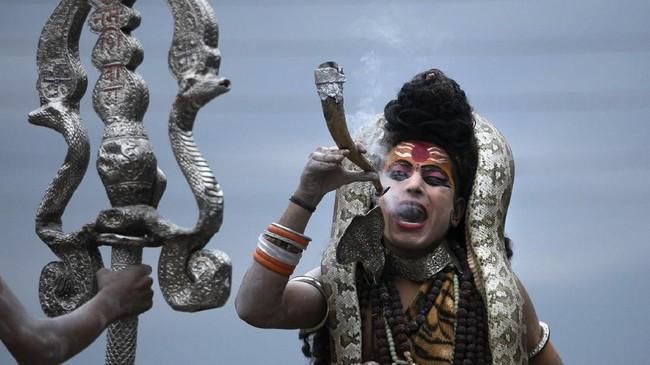 Tak sedikit pengikut yang berdandan bak Dewa Siwa, seperti pria ini yang tak lupa mengalungkan ular di bahu dan membawa pipa. (AP Photo/Channi Anand)
