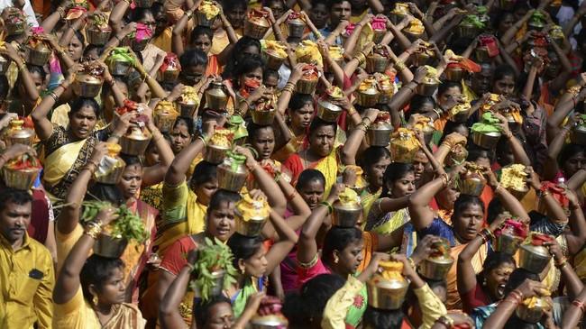 Para pemeluk agama Hindu terlihat mengangkat susu yang diletakkan dalam wadah-wadah, yang akan disajikan untuk Dewa Siwa. (Photo by Arun SANKAR / AFP)