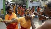 Tak jarang, mereka melakukan sejumlah aksi mencekam, seperti menusuk pipi dengan batang logam. (Photo by Arun SANKAR / AFP)