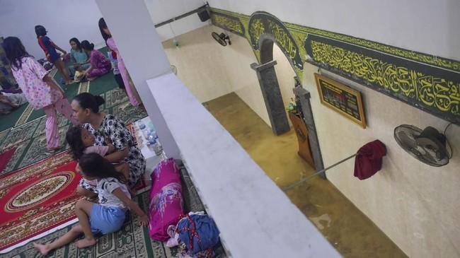Sejumlah warga mengungsi di lantai dua Masjid Jami' Al-Jamaah yang juga terendam banjir di Jalan Anyer, Menteng, Jakarta, Minggu (23/2/2020). Masjid kerap menjadi tempat warga mengungsi kala banjir memasuki rumah. (ANTARA FOTO/M Risyal Hidayat)