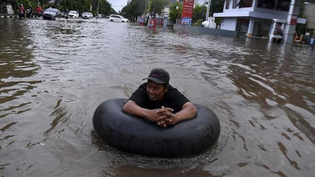 Warga melintasi banjir yang menggenangi kawasan Jalan Danau Sunter Selatan, Sunter Jaya, Jakarta Utara, Minggu (23/2/2020). (ANTARA FOTO/Sigid Kurniawan)