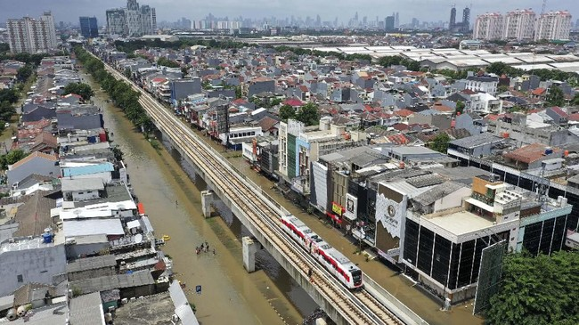 Kereta LRT melintas saat banjir merendam Jalan Boulevard Raya, Kelapa Gading, Jakarta Utara, Minggu (23/2/2020). Hujan deras sejak Minggu, 23 Februari dini hari membuat sejumlah daerah di Ibu Kota tergenang banjir. (ANTARA FOTO/Sigid Kurniawan)