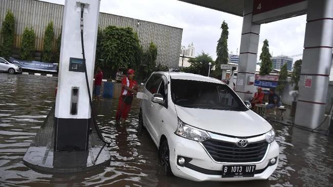 Karyawan melayani pengisian bahan bakar minyak (BBM) saat banjir menggenangi SPBU Pertamina di Jalan Danau Sunter Selatan, Sunter Jaya, Jakarta Utara, Minggu (23/2/2020). (ANTARA FOTO/Sigid Kurniawan)