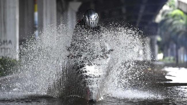 Pengendara sepeda motor mencoba melintasi banjir di Jalan Yos Sudarso, Kelapa Gading, Jakarta Utara, Minggu (23/2/2020). Hujan deras sejak Minggu 23 Februari dini hari membuat sejumlah daerah di Ibu Kota tergenang banjir. (ANTARA FOTO/Sigid Kurniawan)