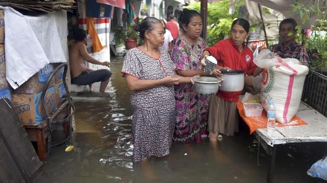 Warga membagikan beras saat banjir merendam di Jalan Anyer, Menteng, Jakarta, Minggu (23/2/2020). (ANTARA FOTO/M Risyal Hidayat)