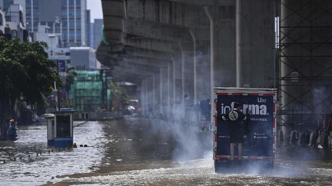 Seorang pria naik ke bagian belakang sebuah truk untuk melintasi banjir di Jalan Boulevard Barat Raya, Kelapa Gading, Jakarta Utara, Minggu (23/2/2020). Banjir yang menerjang Jakarta tersebar di sejumlah wilayah, mulai dari Selatan, Timur dan Utara. (ANTARA FOTO/Sigid Kurniawan)