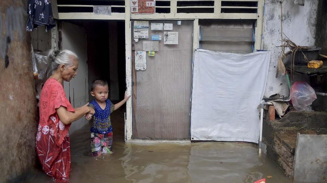 Seorang nenek menuntun cucunya di depan rumahnya yang terendam banjir di Jalan Anyer, Menteng, Jakarta, Minggu (23/2). Menurut warga, sedikitnya 14 RT di lingkungan RW 02 rumahnya terendam banjir akibat tingginya intensitas hujan dan buruknya drainase. (ANTARA FOTO/M Risyal Hidayat)