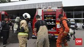 Petugas pemadam kebakaran melepaskan pakaian khusus yang ia kenakan setelah memastikan asap di Gedung Nusantara III bukan berasal darisumberapi.(CNN Indonesia/Safir Makki)