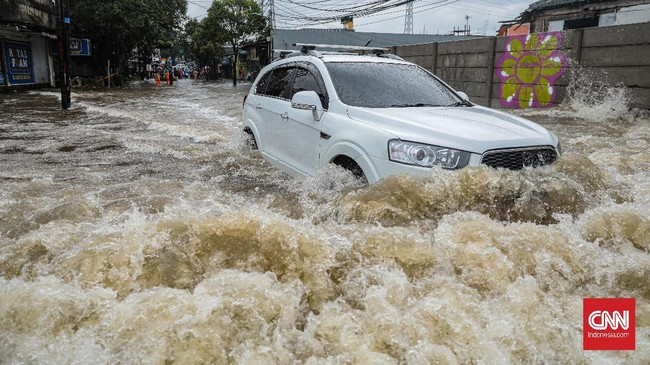 Sejumlah kendaraan nekat menerobos banjir meski berisiko mogok. CNN Indonesia/Bisma Septalisma