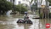 Sejumlah warga mencari jalan yang tidak tergenang untuk mencapai tempat aktivitas. CNN Indonesia/Adhi Wicaksono