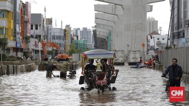 Banjir yang terjadi saat hari kerja membuat warga kesulitan menuju tempat kerja. CNN Indonesia/Adhi Wicaksono