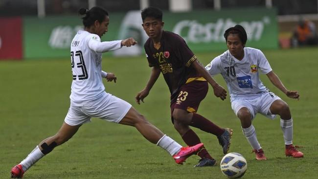 Bayu Gatra (tengah) menirim umpan di tengah adangan dua pemain PSM Makassar. Dia digantikan Rizky Pratama karena mengalami cedera. (ANTARA FOTO/Aditya Pradana Putra/ama)