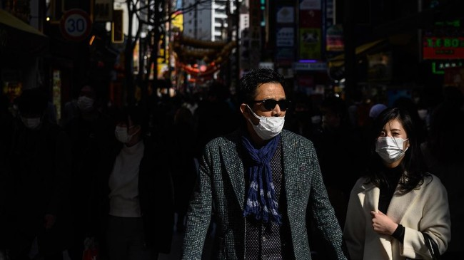 Para pejalan kaki di wilayah Pecinan diYokohama, Jepang, berjalan-jalan menggunakan masker.(Photo by Philip FONG / AFP)