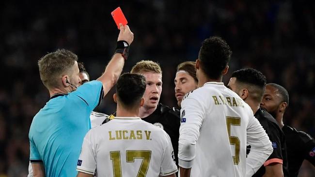 Situasi makin tak menguntungkan Real Madrid setelah Sergio Ramos terkena kartu merah di pengujung laga. (Photo by JAVIER SORIANO / AFP)
