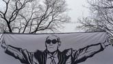 Seorang pendukung membentangkan bendera saat Roger Stone, mantan penasihat Presiden Amerika Serikat Donald Trump, tiba di pengadilan di Washington, DC. (Alex Edelman / AFP)