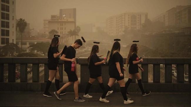Mengenakan kostum, orang-orang terlihat berjalan di tengah kabut merah di sebuah jembatan di Santa Cruz de Tenerife di Spanyol. Penerbangan ke Tenefire terdampak badai pasir merah dari Gurun Sahara. Karnival pada Sabtu sempat dibatalkan, namun keesokan harinya tetap bisa berlangsung. (AP/Andres Gutierrez)