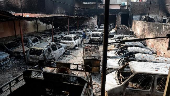 Sehari usai bentrokan, Rabu (26/2) warga mulai membersihkan kerusakan di dalam masjid, termasuk Alquran yang dibakar massa. (Photo by Sajjad HUSSAIN / AFP)