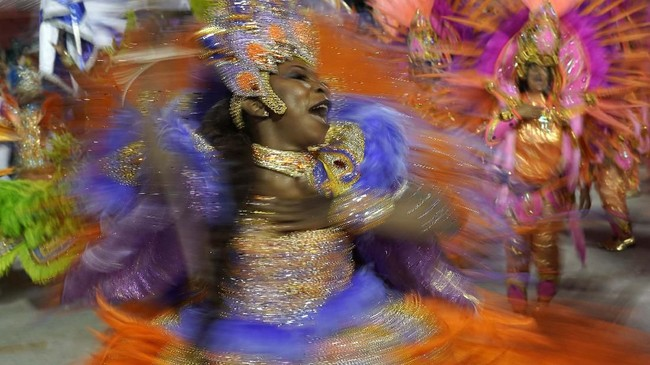 Seorang penari samba unjuk gigi dalam karnaval di Sambadrome, Rio de Janeiro, Brasil. (AP/Leo Correa)