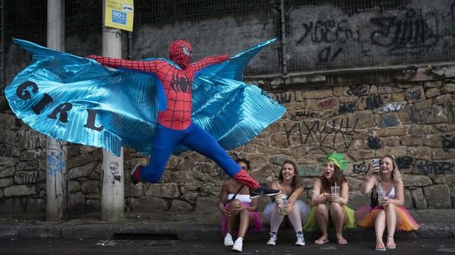 Seorang dalam kostum Spider-Man berpose dalam pesta jalanan