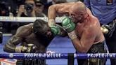 Tyson Fury mendaratkan pukulan telak ke wajah Deontay Wilder. Fury menang TKO di ronde ketujuh setelah sudut ring Wilder melempar handuk. (Photo by John Gurzinski / AFP)