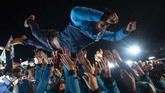 Atlet Prancis, Martin Fourcade meluapkan kegembiraan bersama rekan-rekan setimnya usai menjadi juara 4x7,5 m relay pada IBU Biathlon World Cup. (Photo by MARCO BERTORELLO / AFP)