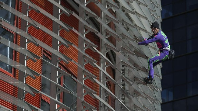Tak lama setelah sampai di puncak gedung setinggi 144 meter atau setara 38 lantai, Robert diamankan oleh pihak kepolisian.(Photo by LLUIS GENE / AFP)
