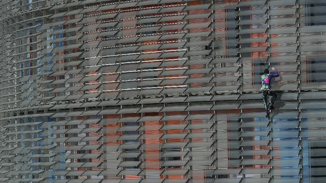 Seperti aksi Robert sebelumnya, kali ini ia memanjat gedung pencakar langit di Barcelona dengan tangan kosong alias tanpa pengaman. (Photo by LLUIS GENE / AFP)