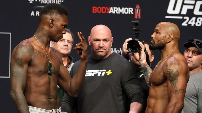 UFC middleweight champion Israel Adesanya, left, of Nigeria, and challenger Yoel Romero, of Cuba, face off during a ceremonial weigh-in for UFC 248 at T-Mobile Arena in Las Vegas, Friday, March 6, 2020. Adesanya will defend his title at the arena on Saturday, March 7. (Steve Marcus/Las Vegas Sun via AP)