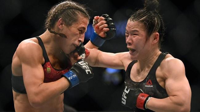 Zhang Weili yang menang split decision atas Joanna Jedrzejczyk membuat Jedrzejczyk babak belur dalam salah satu pertarungan terbaik dalam sejarah UFC di kategori putri. (Harry How/Getty Images/AFP)