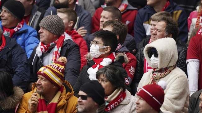 Sejumlah penonton menggunakan masker pada pertandingan Liverpool vs Bournemouth di Stadion Anfield. Isu virus corona membuat Liga Inggris berpeluang digelar tanpa penonton. (AP Photo/Jon Super)