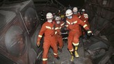 Tim penyelamat mengevakuasi orang yang terluka dalam reruntuhan hotel di Quanzhou, China yang ambruk Sabtu (7/3). Hotel tersebut merupakan lokasi karantina virus corona. (Chinatopix Via AP).