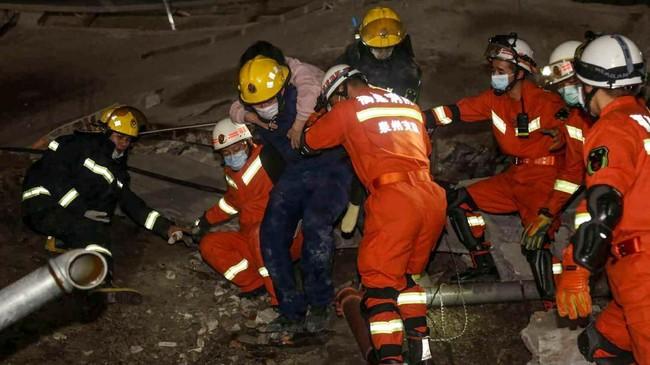 Seorang wanita diselamatkan dari reruntuhan hotel yang digunakan sebagai lokasi karantina virus Corona di Quanzhou, China, Sabtu (7/3). Hotel tersebut ambruk Sabtu (7/3). (Photo by STR / AFP) / China OUT.