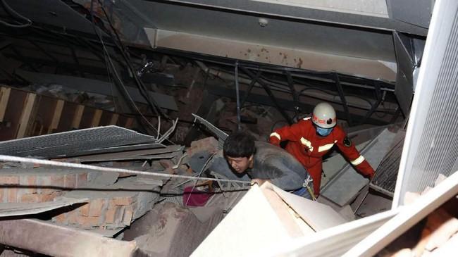 Seorang pria dibantu keluar dari puing sisa reruntuhan hotel di Quanzhou, China. Hotel yang digunaklan untuk karantina virus corona tersebut ambruk Sabtu (7/3). (Chinatopix via AP).