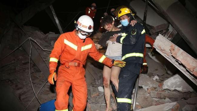 Tim penyelamat membantu seorang wanita yang terjaebak dalam reruntuhan hotel di Quanzhoue, China. Hotel yang digunakan sebagai lokasi karantina tersebut ambruk Sabtu (7/3) dan menimpa puluhan orang. (Chinatopix via AP).