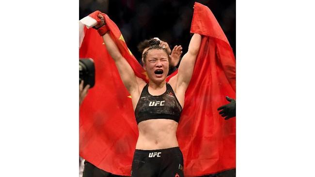 Zhang Weili merayakan kemenangan atas Joanna Jedrzejczyk dengan split 48–47, 48–47, dan 47–48. Pertarungan Zhang vs Joanna ini lebih menarik daripada duel Adesanya vs Romero di kelas menengan UFC. (Harry How/Getty Images/AFP)