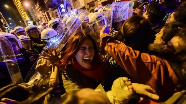 Anggota polisi anti huru-hara Turki mendorong perempuan yang mengikuti aksi unjuk rasa memperingati Hari Perempuan Sedunia di Istanbul. (Photo by Yasin AKGUL / AFP)