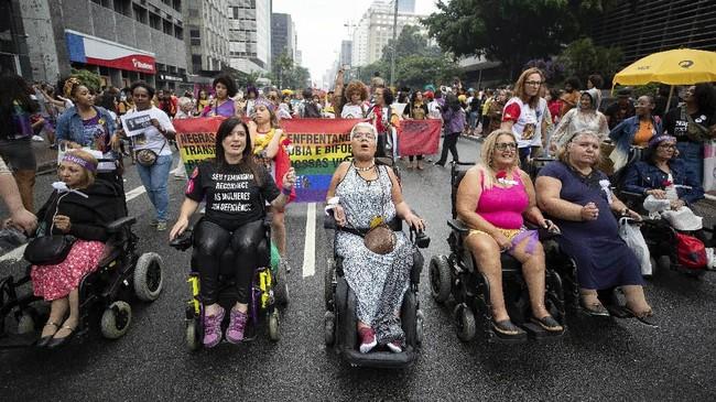 Perempuan Brasil, termasuk kaum penyandang cacat, turun ke jalan memperingati Hari Perempuan Sedunia, Minggu (8/3) kemarin. (AP Photo/Andre Penner)