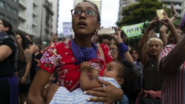 Seorang ibu menyusui anaknya di tengah peringatan Hari Perempuan Sedunia di Ibukota Montevideo, Uruguay. (AP Photo/Matilde Campodonico)