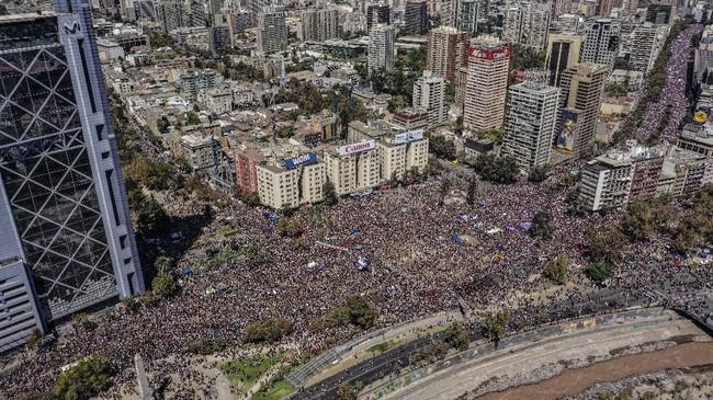 Ribuan warga Chile memenuhi jalan utama Ibukota Santiago memperingati Hari Perempuan Sedunia. Mereka berdemo menuntut emansipasi dan kesetaraan. (Photo by Martin BERNETTI / AFP)
