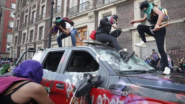 Demonstran di Meksiko merusak mobil pemadam kebakaran saat berunjuk rasa di Hari Perempuan Sedunia. Mereka memprotes tingginya tingkat kekerasan dan pembunuhan terhadap wanita di negara itu. (AP Photo/Rebecca Blackwell)