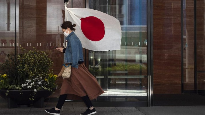 A woman wearing a mask walks past a Japanese flag Wednesday, March 11, 2020, in Tokyo. For most people, the new coronavirus causes only mild or moderate symptoms, such as fever and cough. For some, especially older adults and people with existing health problems, it can cause more severe illness, including pneumonia. The vast majority of people recover from the new virus. (AP Photo/Jae C. Hong)