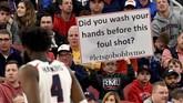 Sebuah poster sindiran yang terkait dengan kebiasaan cuci tangan di tengah isu corona mewarnai pertandingan bola basket antarkampus (NCAA). (Matt Freed/Pittsburgh Post-Gazette via AP)